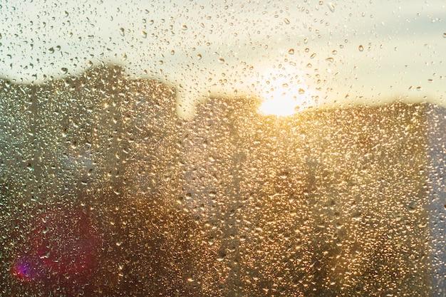 光沢のある雨の滴と背景の日当たりの良い窓、近代的な都市の眺め