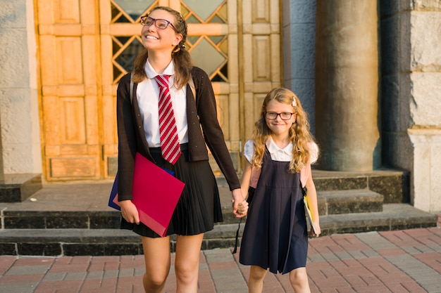 Старшеклассник и ученик начальной школы держатся за руки