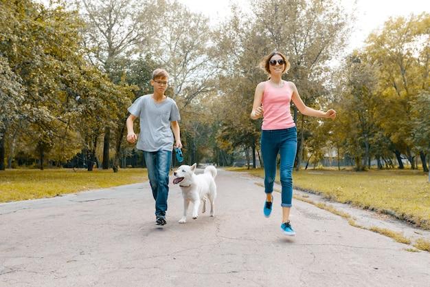 Подростки бегут с белой собакой хаски по дороге в парк