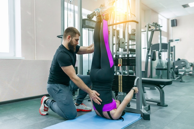 Молодая женщина делает упражнения реабилитации с личным инструктором
