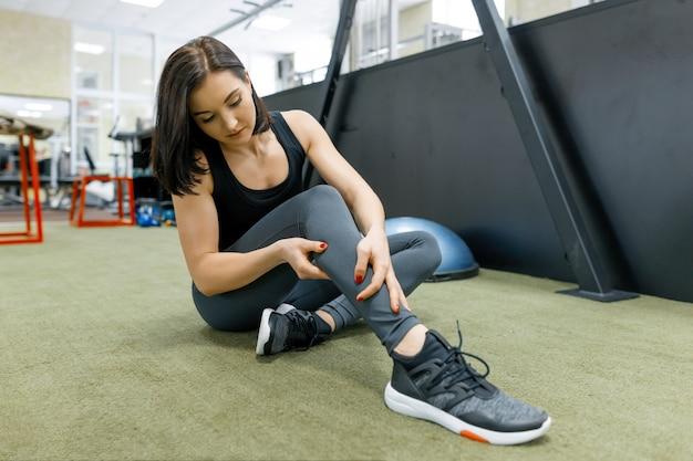 ジムでのエクササイズ後、床で休む若いスポーツ女性