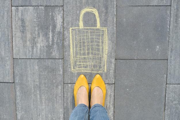 クレヨンで灰色の歩道に書かれたショッピングバッグ画像