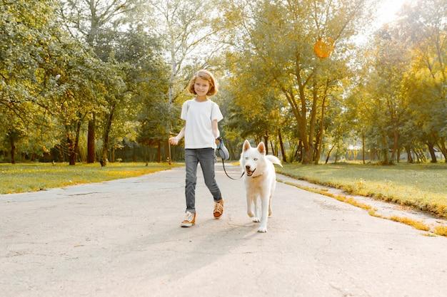 Девушка гуляет по дороге в парке с белой собакой хаски