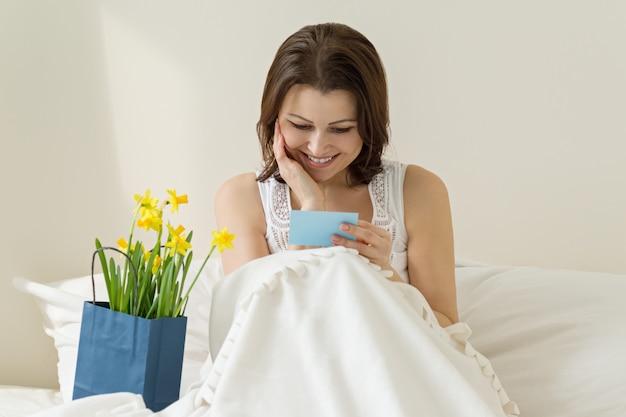 Счастливая зрелая женщина наслаждаясь подарком цветков и читая поздравительную открытку