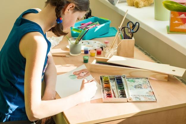 Девочка-подросток, рисование акварелью за столом в комнате