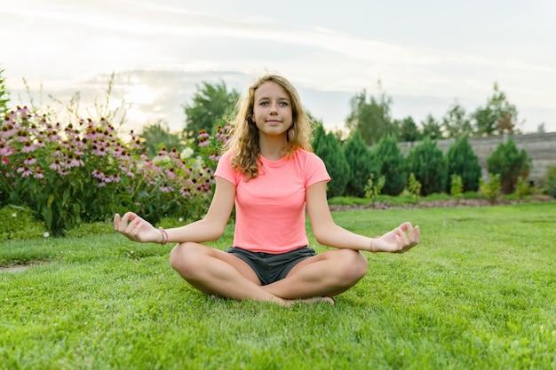 Молодая девушка практикующих йогу, медитируя на летний закат