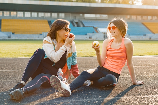Улыбаясь фитнес мать и дочь-подросток вместе едят яблоко