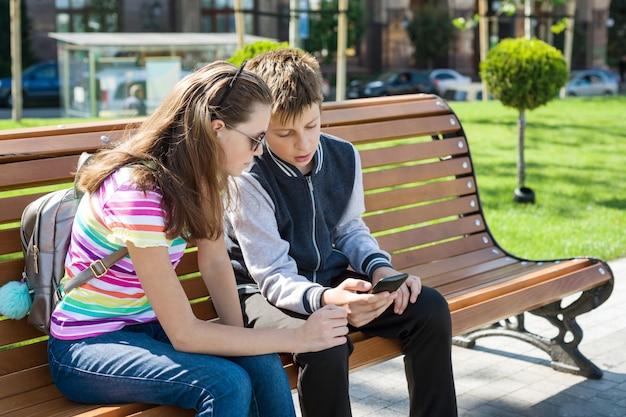 男の子と女の子のティーンエイジャーが遊ぶ、スマートフォンを見て