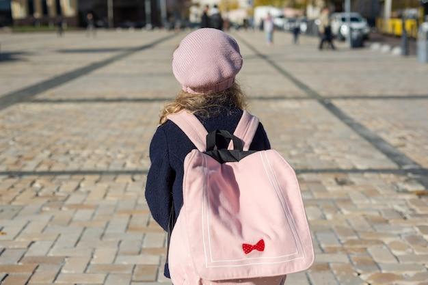 Стильная маленькая девочка с рюкзаком, в пальто и французском берете бежит в школу.
