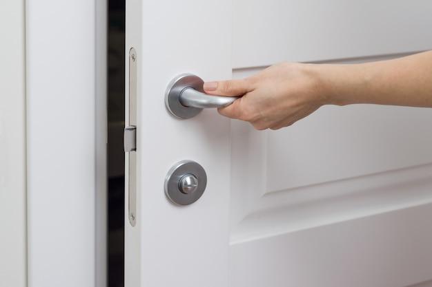 女性の手のクローズアップが開き、白いインテリアのドアを閉じます