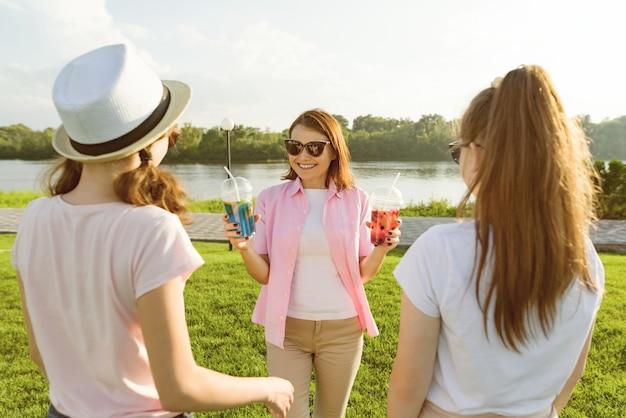 Мама активно отдыхает на природе со своими дочерьми-подростками.