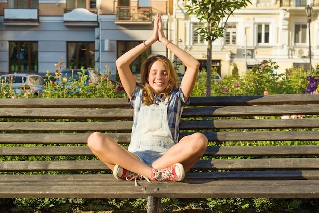Йога в городе, девушка сидит в позе лотоса на скамейке в городском парке.