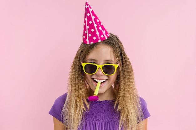 パイプで吹くお祝い帽子の女の子