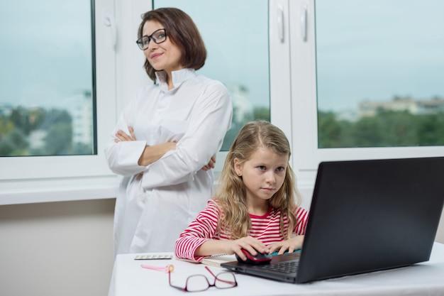 医者のオフィスの子供患者はテーブルに座って、ノートパソコンを見て
