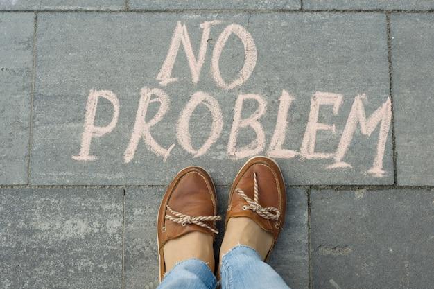 Женские ноги с текстом без проблем написаны на сером тротуаре
