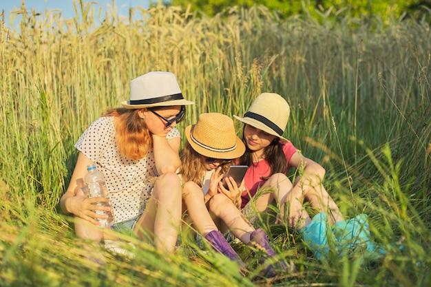 Портрет трех девушек, сидящих и отдыхающих в траве