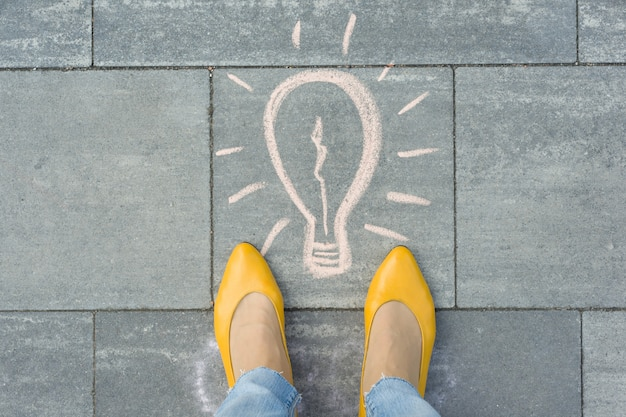 Женские ноги с рисунком лампочки написано на сером тротуаре