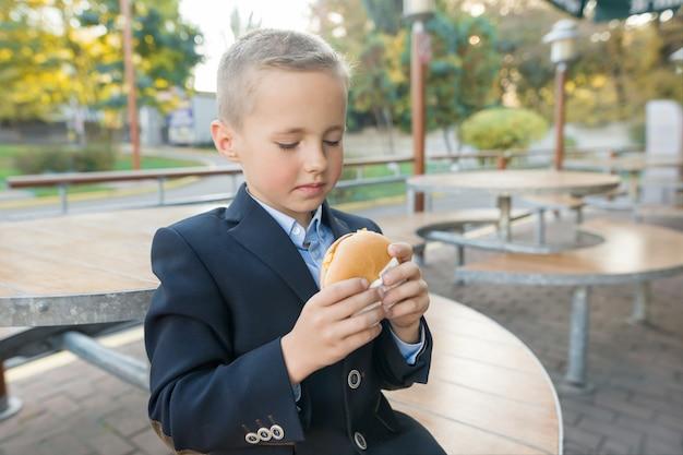 Мальчик ученик начальной школы ест гамбургер, бутерброд в уличном кафе