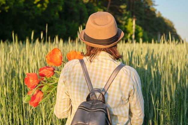赤いケシの花束と幸せな成熟した女性の屋外のポートレート