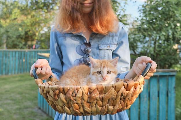 Маленький рыжий котенок в корзине, девушка держит корзину, деревенский стиль