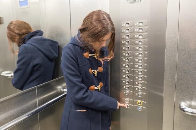 Молодая девушка в лифте, нажимает кнопку лифта