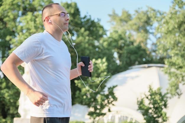 アクティブな健康的なライフスタイル、公園で走っている中年の男