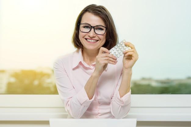 彼女の手で丸薬を保持している肖像画の女性