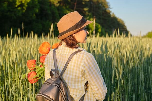 ケシの花束を持つ成熟した女性の屋外のポートレート