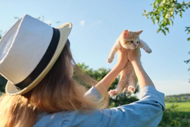 Молодая девушка держит маленький рыжий котенок в саду