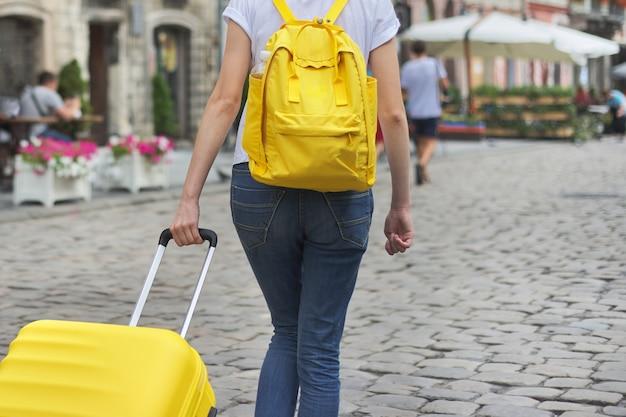 Девушка гуляет с рюкзаком и чемоданом на город, вид сзади