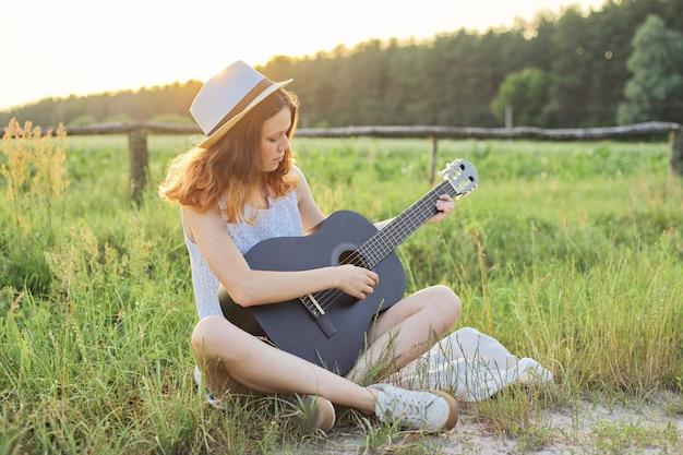 Девушка подростка в шляпе играя предпосылку природы гитары