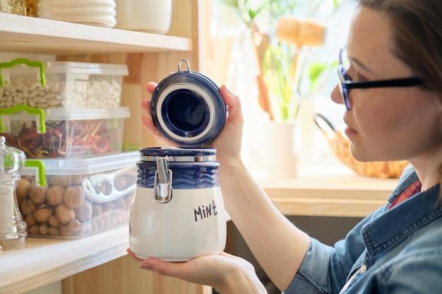 ドライミントの缶が付いている台所の女性