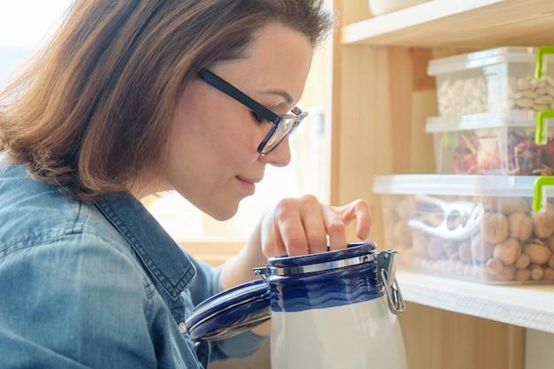 食品を保存するための缶が付いている木製のラックの近くのキッチンで女性
