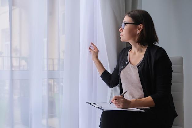 成熟した女性ソーシャルワーカー、心理学者、クリップボードと窓の近くに座っています。