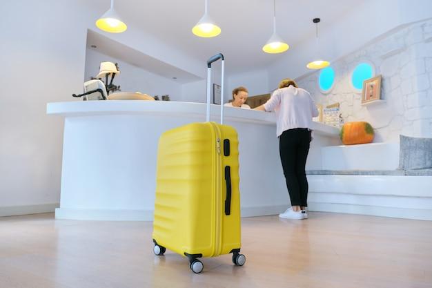 Желтый чемодан возле стойки регистрации в холле гостиницы