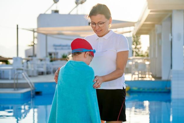 プールの近くのタオルで泳ぐための帽子ゴーグルで母と娘の子供