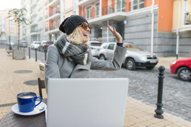 Фрилансер блоггера молодой женщины в внешнем кафе с компьютером