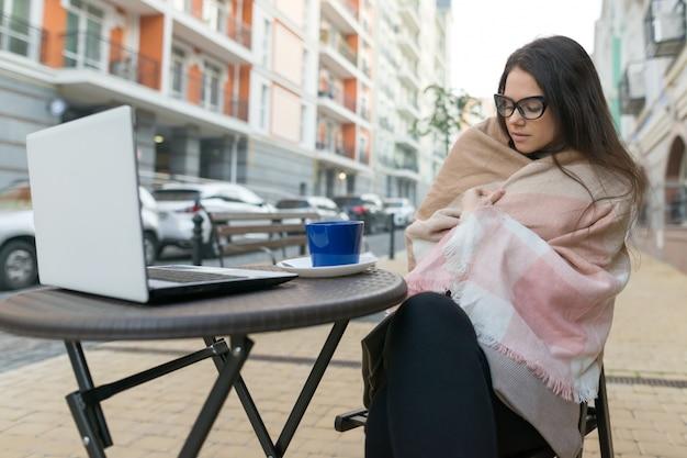 Молодая женщина студент с очками в открытом кафе с ноутбуком