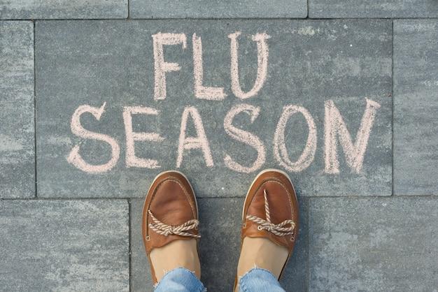 Женские ноги с текстом сезон гриппа написано на сером тротуаре