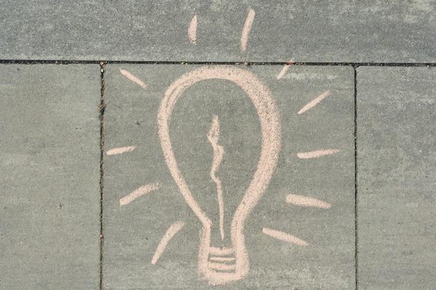 Абстрактный рисунок рисунок лампочки написано на сером тротуаре