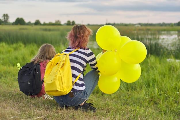 自然の中で風船を持つ二人の女の子、湖の近くの子供たち
