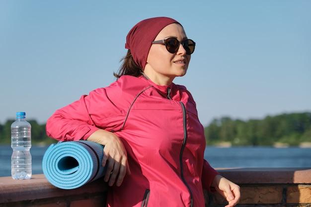 ヨガマットと水のボトルを持つ中年のスポーツの女性