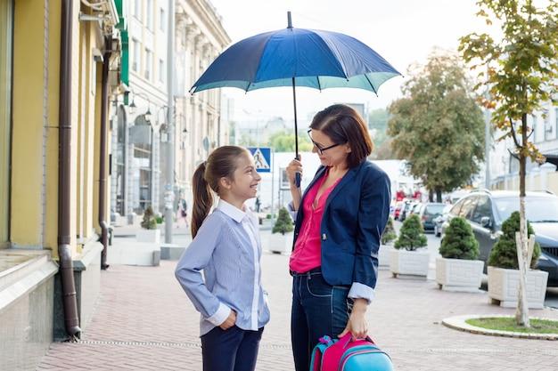 学校に一緒に歩いている娘を持つ女性