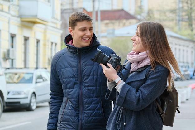 カメラが付いている都市の若い男性と女性のブロガーの若い肯定的なカップル