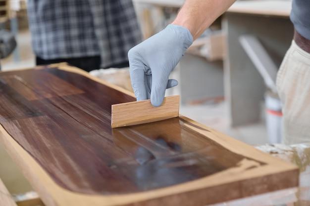 木の保護カバーを仕上げで木の板をカバーする労働者の手のクローズアップ
