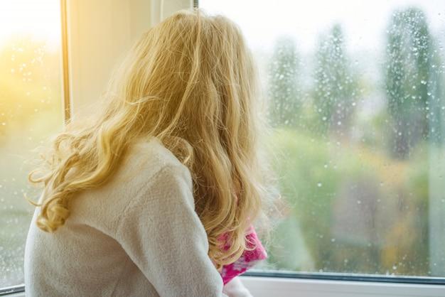 雨の滴を秋の窓で見ている子
