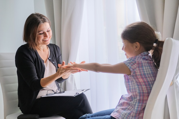 Говорят девушка и женщина психотерапевт в офисе возле окна