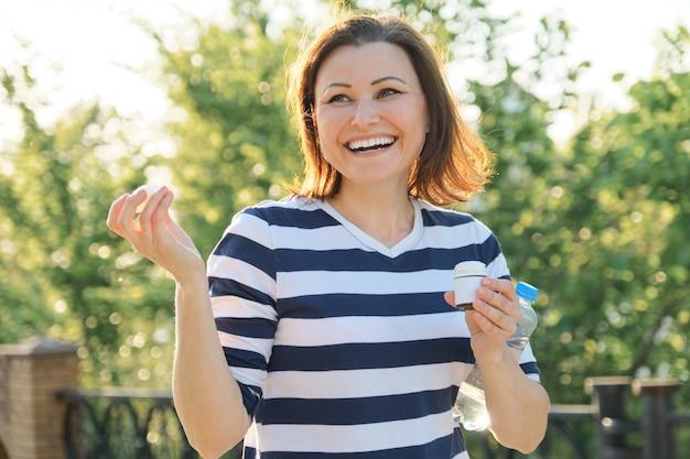 薬、ビタミン、サプリメントを持つ屋外の中年女性