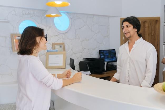 リゾートホテルのフロント、フロントで働いている男と話している女性ゲスト