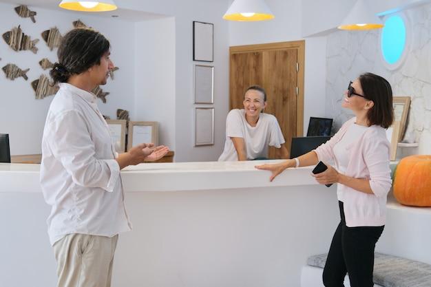 フロント、フレンドリーな男性と女性のホテル労働者の近くの女性ゲストの笑顔
